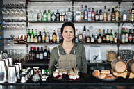 Portrait of confident female owner with dessert standing at counter in restaurant - MASF07467
