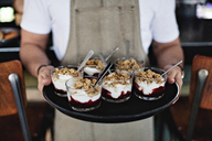 Midsection of owner holding dessert in tray while standing at counter in restaurant - MASF07491