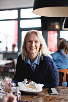 Portrait of smiling mature woman sitting at dining table in restaurant - MASF07524