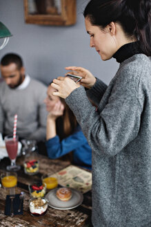Young woman photographing food on dining table at restaurant - MASF07533