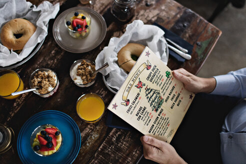 Midsection of man holding menu while having brunch at dining table - MASF07545