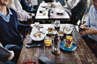 Mature man using mobile phone while having brunch with family at table - MASF07554