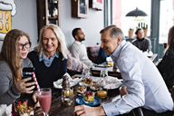 Smiling daughter taking selfie with parents while sitting at table in restaurant - MASF07557