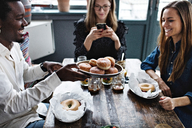 Smiling man giving buns to friend while woman using mobile phone at table - MASF07563