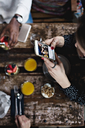 High angle view of woman photographing food through smart phone at table - MASF07569
