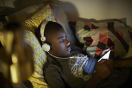 High angle view of boy wearing headphones and using digital tablet while lying on bed - MASF07581