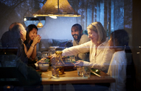 Happy family enjoying while having dinner at table seen through glass window - MASF07590