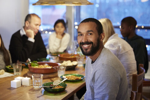 Portrait of smiling father sitting with family during meal at table - MASF07593
