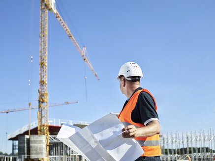 Construction worker with blueprint on construction site - CVF00334