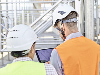 Architect and foreman with tablet wearing hards hat on construction site - CVF00340