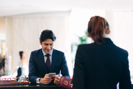 Businessman checking in at hotel reception - CUF00063