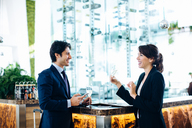 Businessman and businesswoman having drink at bar - CUF00075