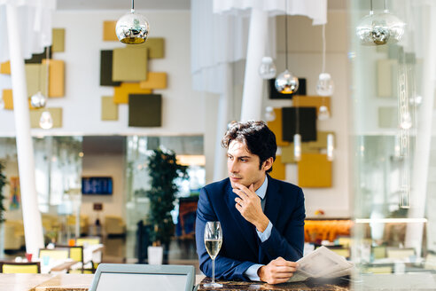 Businessman reading the newspapers while having drink at bar - CUF00078