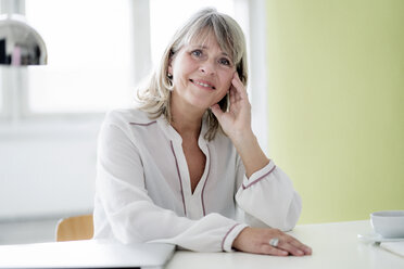 Portrait of smiling mature businesswoman at desk - HHLMF00244