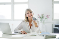 Happy mature businesswoman using cell phone at desk - HHLMF00247
