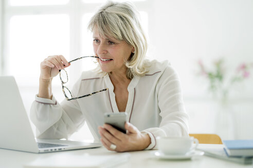 Mature businesswoman holding cell phone working on laptop at desk - HHLMF00250