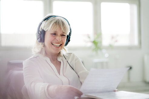 Laughing mature businesswoman wearing headphones looking at document at desk - HHLMF00253