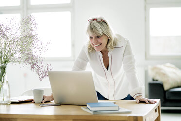 Smiling mature businesswoman working on laptop at desk - HHLMF00259