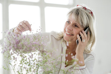Smiling mature woman on cell phone caring for flowers - HHLMF00262