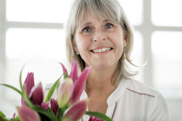 Portrait of smiling mature woman holding bunch of flowers - HHLMF00265