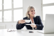 Smiling mature businesswoman with cup of coffee working on laptop at desk in the office - HHLMF00274