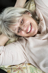 Happy mature woman lying down relaxing - HHLMF00283
