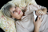 Smiling mature woman lying down with cell phone and earphones - HHLMF00286