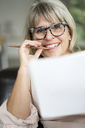 Portrait of smiling mature woman holding pen and sketchbook - HHLMF00289