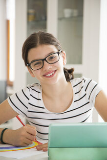 Portrait of smiling girl drawing at home - LVF06919