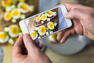 Man holding smartphone with photo of vegetarian breakfast with bread and eggs - GIOF03945