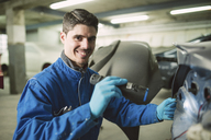 Portrait of smiling mechanic inspecting a car with a torch in a workshop - RAEF01994