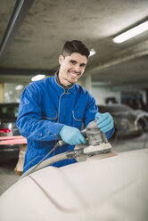 Portrait of smiling man polishing the hood of a car in a workshop - RAEF02000