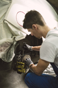 Mechanic fixing the brake caliper of a car in a workshop - RAEF02003