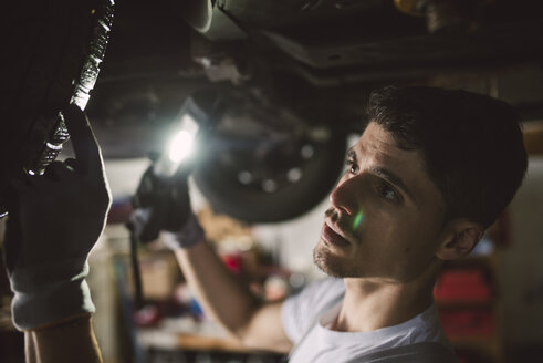 Mechanic checking the underbody of a car in a workshop - RAEF02006