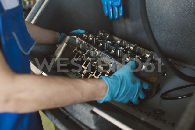 Detail of mechanic working on an engine in his workshop - RAEF02009