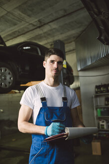 Mechanic with clipboard and checklist in his workshop - RAEF02021