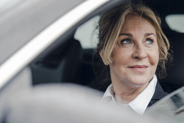 Portrait of smiling senior businesswoman in car - KNSF03815