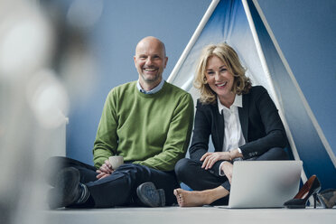 Happy businessman and businesswoman sitting at teepee indoors with laptop - KNSF03818