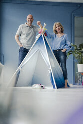 Smiling couple standing at teepee indoors - KNSF03824