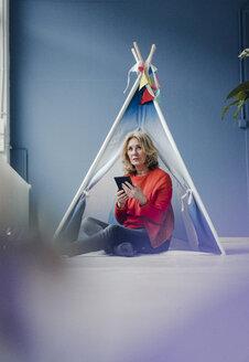 Senior woman sitting at teepee indoors holding phablet - KNSF03836