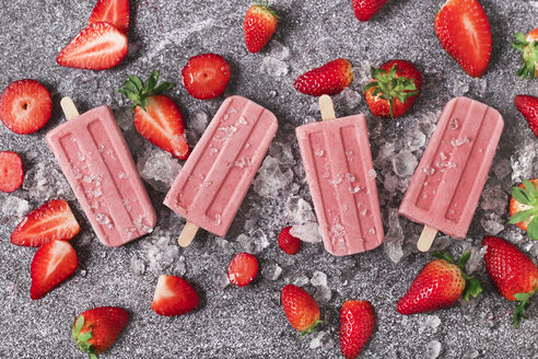 Four homemade strawberry ice lollies, ice and strawberries on marble - RTBF01251