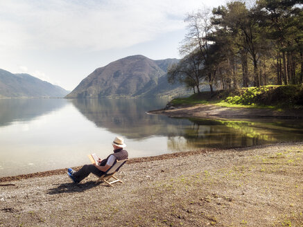 Italy, Lombardy, senior man sitting at Lake Idro using tablet - LAF02016