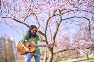 Happy young woman with guitar in a park at cherry blossom tree - BEF00021