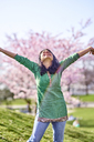 Happy young woman in a park at cherry blossom tree - BEF00024