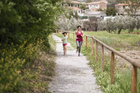 Mother and daughter running on a path in nature enviroment - JSMF00175