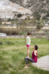Mother and daughter doing yoga on boardwalk - JSMF00178