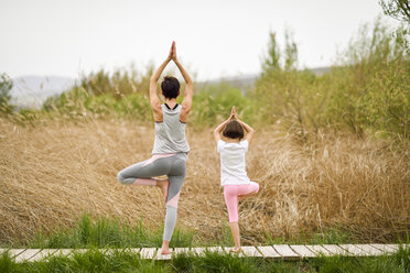 Rear view of mother and daughter doing yoga on boardwalk - JSMF00181