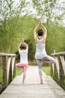 Rear view of mother and daughter doing yoga on boardwalk - JSMF00187