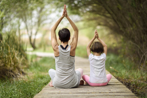 Rear view of mother and daughter doing yoga on boardwalk - JSMF00190