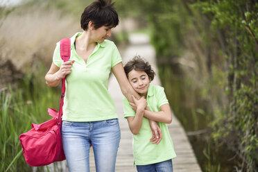 Mother and affectionate daughter walking on boardwalk - JSMF00199
